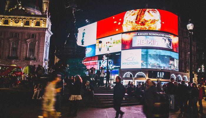 Crowd of people under digital billboards